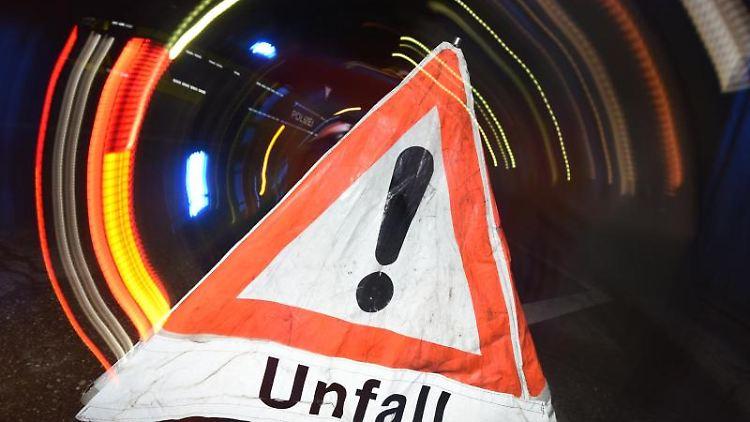 Ein Warndreieck steht vor einem Blaulicht auf der Straße. F. Foto: Patrick Seeger/dpa