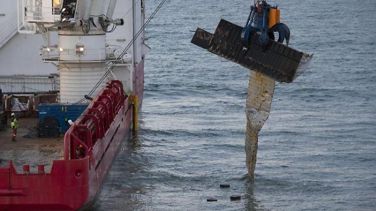 Ein Bergungsschiff hebt einen Container vom Meeresboden. Foto: Peter Dejong/AP/dpa