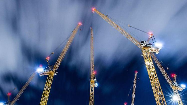 Wolken ziehen über Baukräne auf einer Großbaustelle hinweg. Foto: Silas Stein/dpa/Archivbild