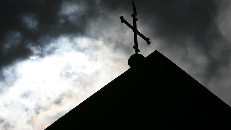 Im Gegenlicht und vor wolkenverhangenem Himmel ist die Spitze eines Krichturms zu sehen. Foto: Friso Gentsch/dpa/Archivbild