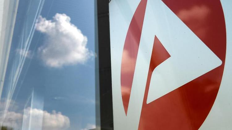 Das Logo eines Jobcenters spiegelt sich am Eingang. Foto: Jens Kalaene/zb/dpa