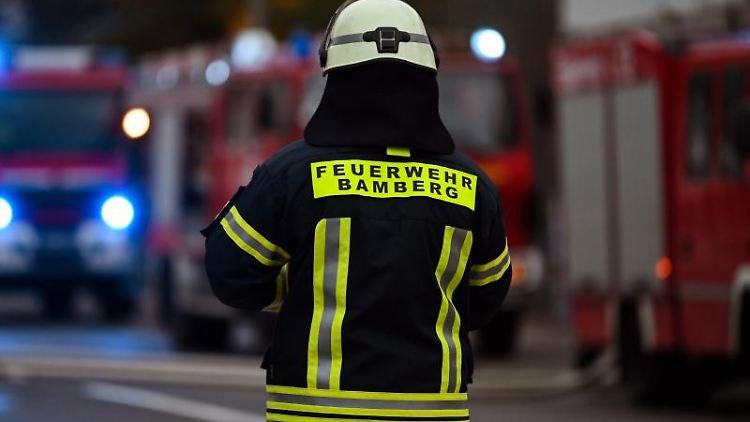 Ein Feuerwehrmann steht bei Nachlöscharbeiten vor mehreren Feuerwehreinsatzfahrzeugen. Foto: Nicolas Armer/dpa/Archivbild