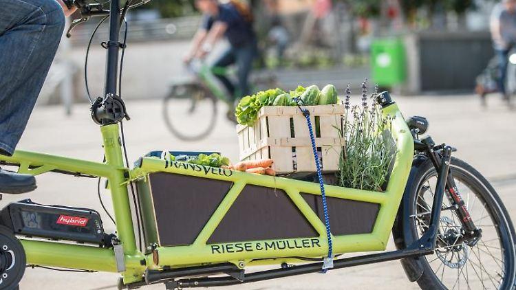 Ein Mann transportiert Lebensmittel auf einem mit einem Elektromotor unterstützten Lastenfahrrad. Foto: Wolfram Kastl/dpa/Archivbild