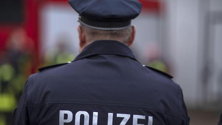 Polizisten stehen vor einem Polizeifahrzeug. Foto: Jens Büttner/zb/dpa/Archiv