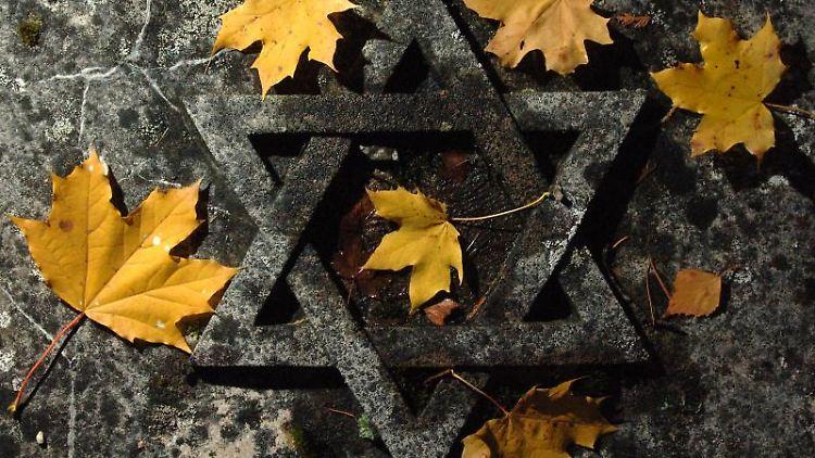 Herbstlaub auf einer Grabplatte mit einem Davidstern auf dem jüdischen Friedhof in Erfurt. Foto: Martin Schutt/dpa-Zentralbild/dpa/Archivbild