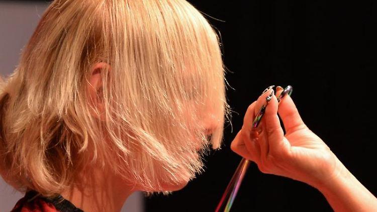 Ein Haarmodel bekommt einen Haarschnitt verpasst. Foto: Marc Tirl/dpa-Zentralbild/dpa/Archivbild