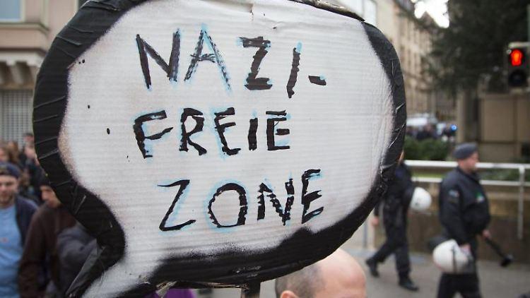 Ein Teilnehmer hält bei einer Demonstration ein Schild mit der Aufschrift