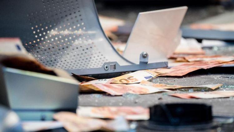 Geldscheine und Metallteile liegen in einer Bankfiliale, in der ein Geldautomat gesprengt wurde. Foto: Matthias Balk/dpa