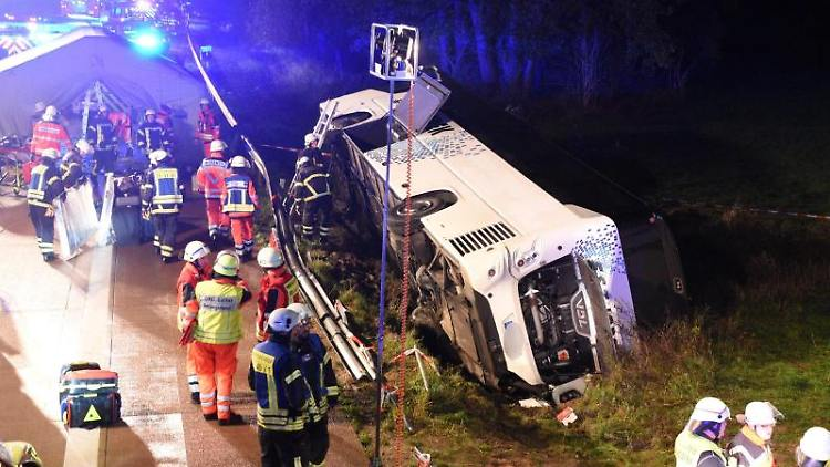 Ein Bus liegt neben der Autobahn im Graben, Einsatzkräfte stehen daneben. Foto: Daniel Bockwoldt/dpa