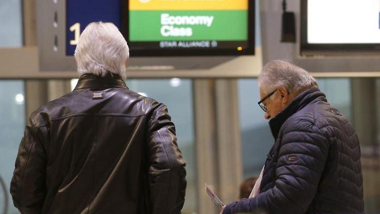 Passagiere warten im Flughafen Düsseldorf. Foto: David Young/dpa