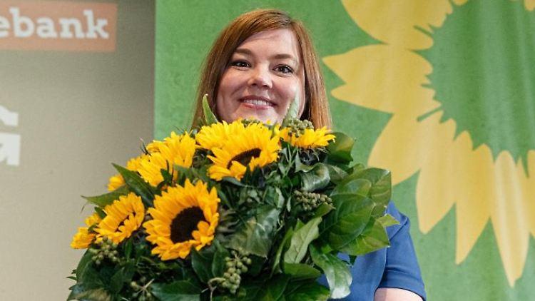 Katharina Fegebank (Die Grünen) hält lächelnd einen Blumenstrauß. Foto: Markus Scholz/dpa