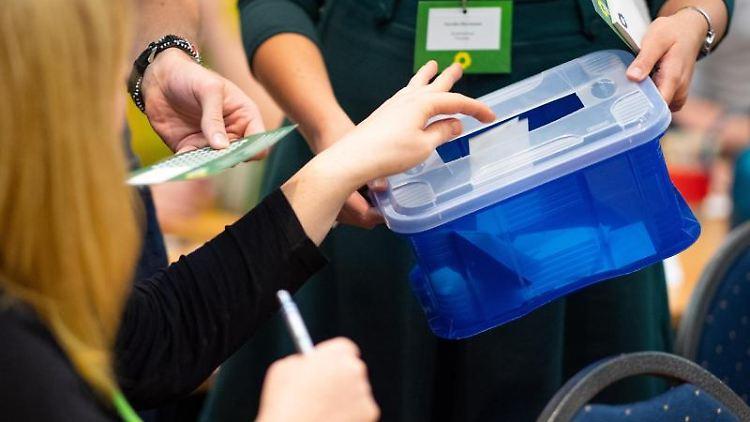 Eine Delegierte wirft auf dem Parteitag von Bündnis 90/Die Grünen ihren Stimmzettel in die Urne. Foto: Monika Skolimowska/dpa-Zentralbild/dpa