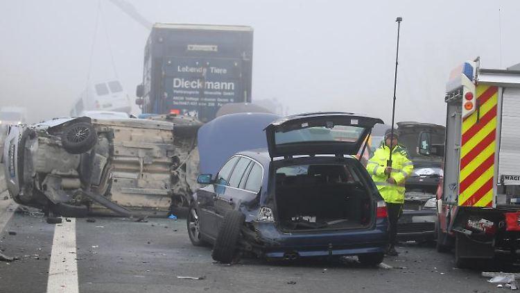 Demolierte Fahrzeuge stehen an einer Unfallstelle auf der A7 auf einer Brücke im Nebel. Foto: Karl-Josef Hildenbrand/dpa