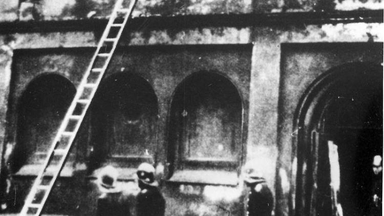 Feuerwehrleute vor einer Synagoge in Berlin am 10. November 1938. Foto: Uncredited/AP/dpa/Archivbild