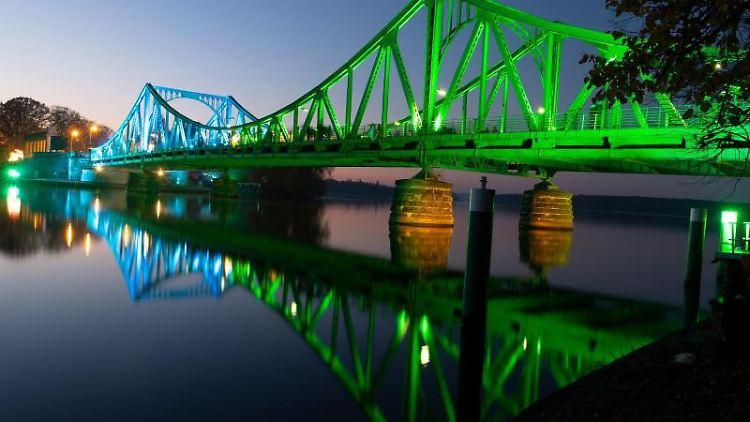 Die Glienicker Brücke ist anlässlich des 30. Jahrestags des Mauerfalls festlich beleuchtet. Foto: Monika Skolimowska/dpa-Zentralbild/dpa