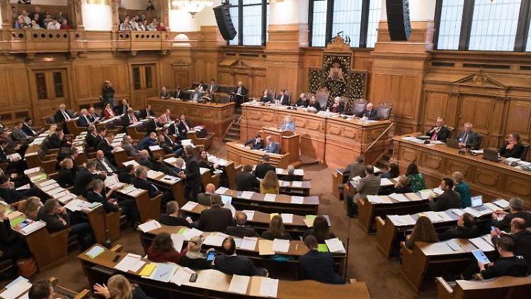 Abgeordnete verfolgen im Rathaus die Sitzung der Hamburgische Bürgerschaft. Foto: Daniel Reinhardt/dpa