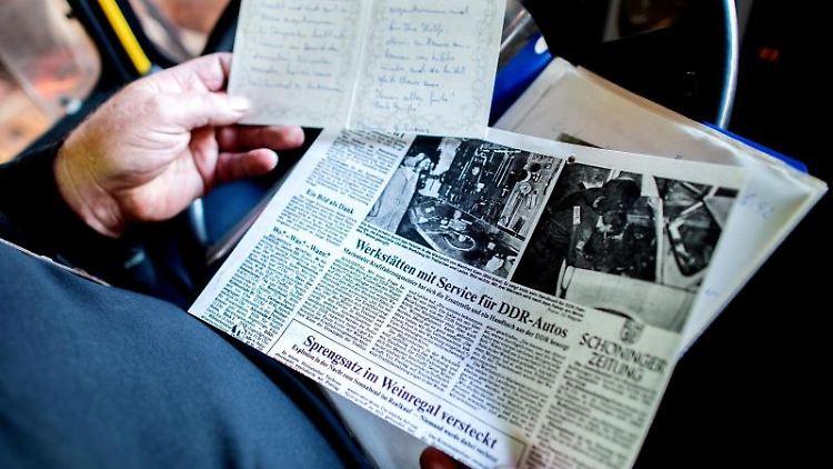 Manfred Klein, ehemaliger Pannenhelfer, betrachtet alte Zeitungsausschnitte und Briefe. Foto: Hauke-Christian Dittrich/dpa/Archivbild