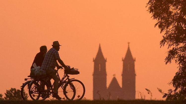 Ein älteres Ehepaar fährt vor der Silhouette des Magdeburger Doms mit dem Fahrrad über den Deich. Foto: Lukas Schulze/dpa/Archivbild
