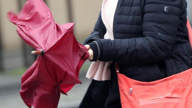 Bei stürmischem und regnerischem Wetter haben Menschen Probleme ihre Regenschirme zu bändigen. Foto: Wolfgang Kumm/dpa/Archivbild