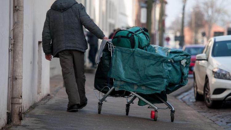 Ein obdachloser Mann schiebt einen Einkaufswagen, samt Planen, Rucksack und Tasche durch die Stadt. Foto: Philipp Schulze/dpa/Archivbild