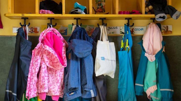 Jacken und Taschen hängen im Eingangsbereich in einem Kindergarten. Foto: Monika Skolimowska/zb/dpa/Archivbild