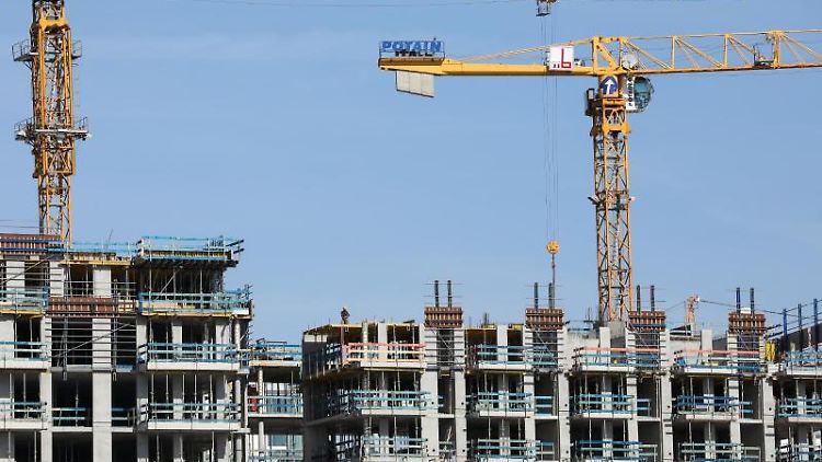 Kräne stehen auf einer Baustelle für mehrstöckike Wohnhäuser. Foto: Christian Charisius/dpa/Archivbild