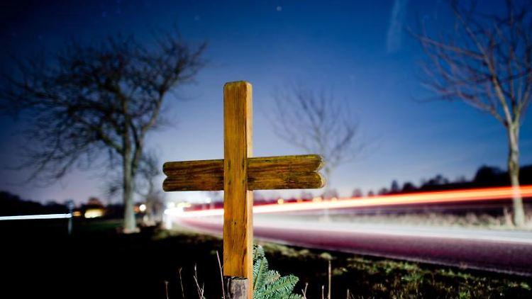 Ein Kreuz zur Erinnerung an einen Verkehrstoten steht an einer Landstraße. Foto: Julian Stratenschulte/dpa/Archivbild