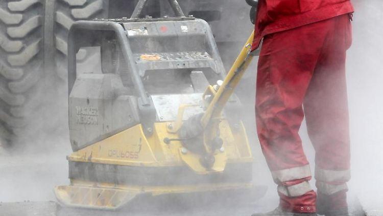 Bauarbeiter reparieren eine Straßendecke. Foto: Roland Weihrauch/Archiv