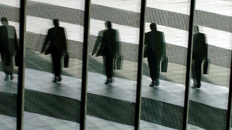 Ein Mann mit Aktentasche geht ins Büro und spiegelt sich dabei in den Glasscheiben. Foto: Oliver Berg/dpa