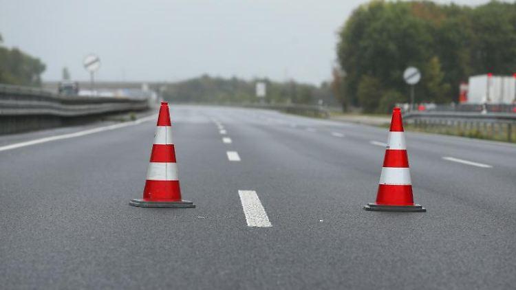 2 Verkehrshütchen stehen mitten auf einer gesperrten Autobahn. Foto: David Young/dpa/Archivbild
