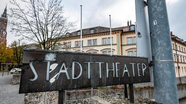 """Ein Schild mit der Aufschrift """"Stadttheater"""" steht vor dem sanierungsbedürftigen Gebäude. Foto: Armin Weigel/dpa"""