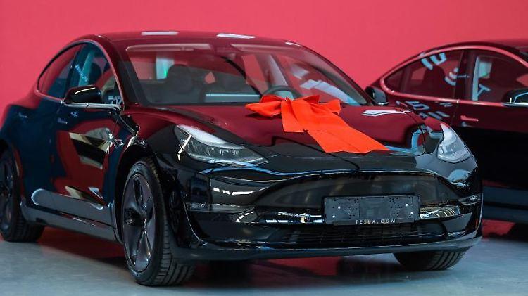 Ein Tesla Model 3 mit einer roten Schleife auf der Kühlerhaube. Foto: Silas Stein/dpa/Archivbild