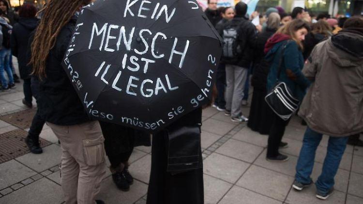 Eine Frau hält während einer Demonstration einen Regenschirm mit der Aufschrift