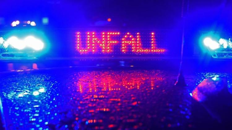 Während einer Unfallaufnahme spiegeln sich das Blaulicht und der Schriftzug