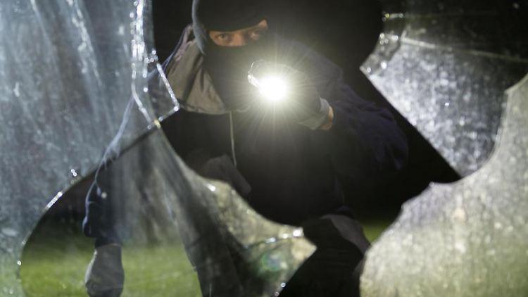 Ein fiktiver Einbrecher blickt an einem Haus durch eine eingeschlagene Fensterscheibe. Foto: Daniel Maurer/dpa/Archivbild
