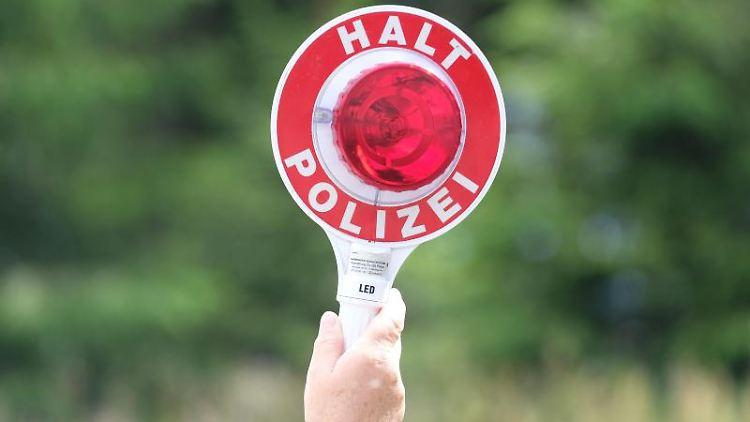 Eine Polizistin hält eine Winkerkelle in die Höhe. Foto: Sebastian Willnow/zb/dpa/Archivbild