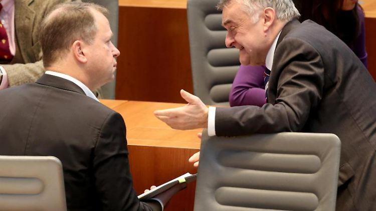 Familienminister Joachim Stamp (FDP (l) unterhält sich mit Innenminister Herbert Reul (CDU). Foto: Roland Weihrauch/dpa/Archivbild