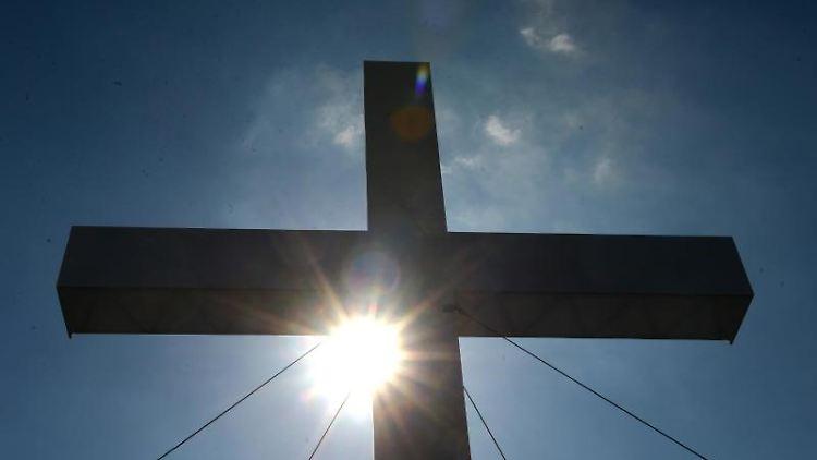 Ein Kreuz im Sonnenlicht. Foto: Marcus Brandt/dpa/Symbolbild