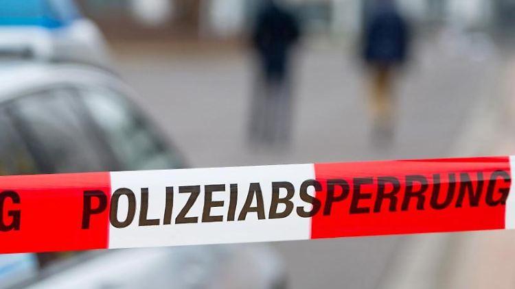 Ein Polizeiabsperrband vor einem Polizeiwagen. Foto: Marc Tirl/ZB/dpa/Symbolbild