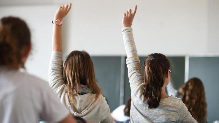 Schüler melden sich während des Unterrichts in einem Gymnasium. Foto: Felix Kästle/dpa