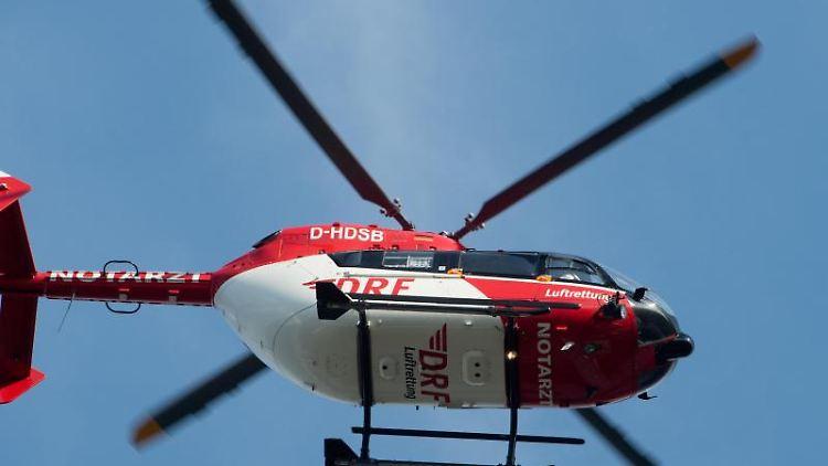 Ein Rettungshubschrauber fliegt über einen Flugplatz. Foto: Stefan Sauer/zb/dpa