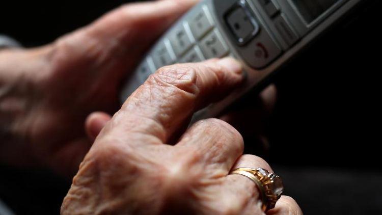 Eine ältere Frau tippt auf einem schnurlosen Festnetztelefon. Foto: Karl-Josef Hildenbrand/dpa/Archivbild