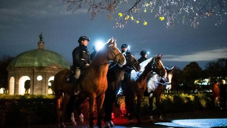 Polizisten auf Pferden bewachen das Bundeswehr-Gelöbnis im Münchner Hofgarten. Foto: Matthias Balk/dpa