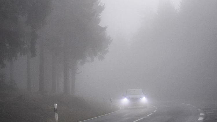 Langsam fährt ein Auto durch den dichten Nebel im Taunus. Foto: Boris Roessler/dpa