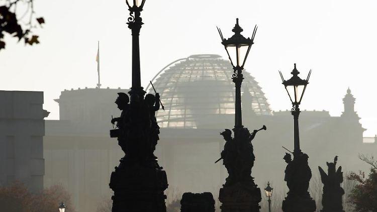 Die Laternen und steinernen Figuren der Moltkebrücke rahmen im morgendlichen Gegenlicht den Reichstag ein. Foto: Soeren Stache/dpa-Zentralbild/dpa
