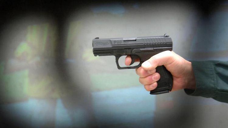 Ein Polizist zielt in Duisburg mit einer Walther P 99-Pistole in der Hand. Foto: Federico Gambarini/dpa/Archivbild
