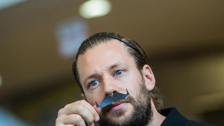"""Marco Russ hält sich einen Papier-Schnurrbart, Symbol der """"Movember Foundation"""" vor sein Gesicht. Foto: Andreas Arnold/dpa"""