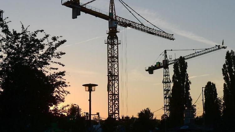 Baukräne am Abend in der Dämmerung bei untergehender Sonne. Foto: Jens Kalaene/ZB/dpa/Archivbild