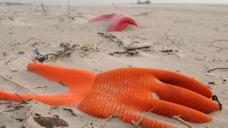 Angespülter Unrat in Form eines Arbeitshandschuhs und eines Kunststoffkanisters liegt am Strand. Foto: Ingo Wagner/dpa/Archivbild