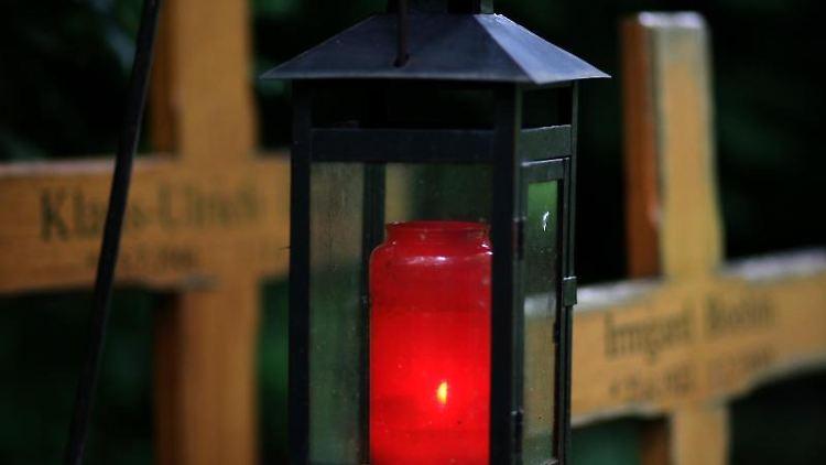 Ein Grablicht leuchtet auf einem Friedhof.. Foto: Heiko Lossie/dpa